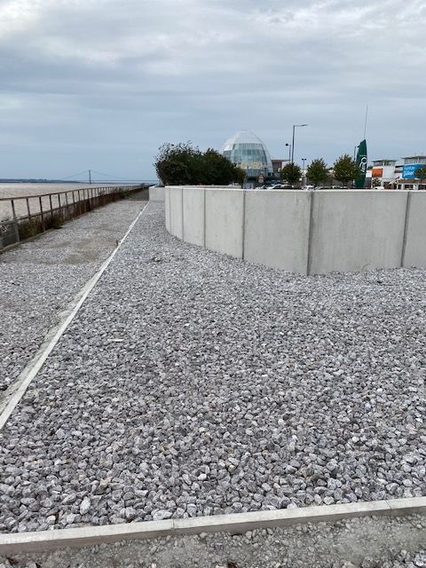 August 2020: The Environment Agency fill gravel around the 'bow shape' flood defence wall